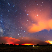 The Milli Fire illuminates the clouds and mountains as it burns late Friday, Aug. 18, 2017, night near Sisters. (Ryan Brennecke/Bulletin photo)
