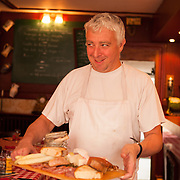 Chef Stephane Bellan holds a cheese and meat board appetizer at Chez Mamie, a restaurant serving traditional French cusine.
