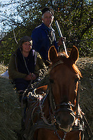 Farmer couple on a horse carriage loaded with hay in the village of Isverna. Geoparcul Platoul Mehedinți, Romania.