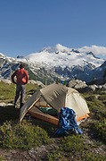 Adult male in red shirt at backcountry camp near Middle Lakes. Mount Challenger and Whatcom Peak seen in the distance. North Cascades National Park Washington