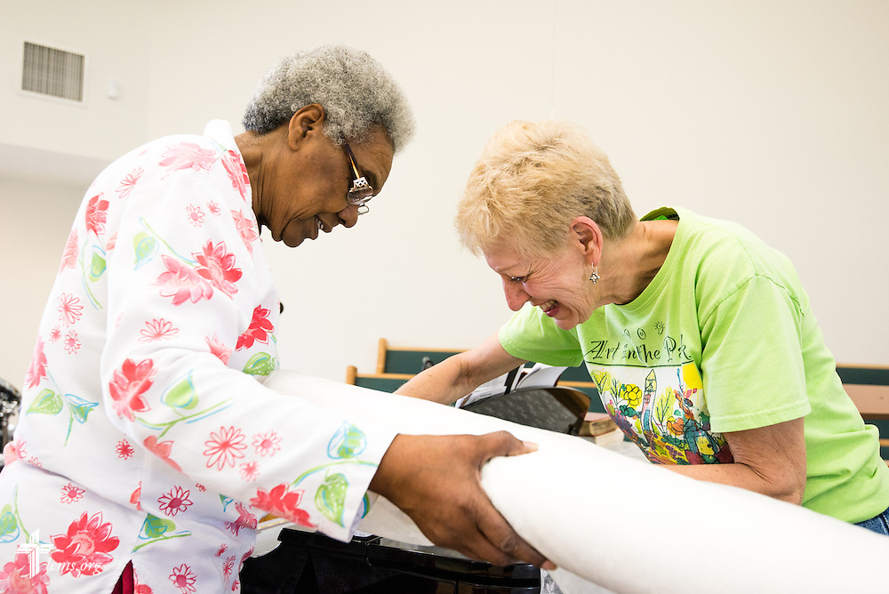 Geraldine Parker of St. Matthew Lutheran Church and Sally Dunham of St. Paul's Lutheran Church in Foley, Ala., cut fabric to cover the piano in the sanctuary of St. Matthew Lutheran Church on Saturday, May 3, 2014, in Pensacola, Fla.  Torrential rainfall led to widespread flooding in the area, damaging the fellowship hall and sanctuary of St. Matthew. LCMS Communications/Erik M. Lunsford