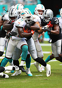 Sep 23, 2018; Miami Gardens, FL, USA; Miami Dolphins running back Frank Gore (21) fights for yardage at Hard Rock Stadium between the Miami Dolphins and the Oakland Raiders. The Dolphins defeated the Raiders 28-20. (Steve Jacobson/Image of Sport)