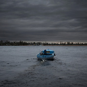 Locals cross the Dnieper river by boat in Kherson, a region bordering Crimea.