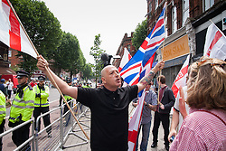 """Cricklewood, London, July 19th 2014. One of 13 protesters from the far right """"South East Alliance"""" gestures at scores of anti-fascists conter protesting their anti-Islamists' demonstration outside the London offices of Egypt's Muslim Brotherhood."""