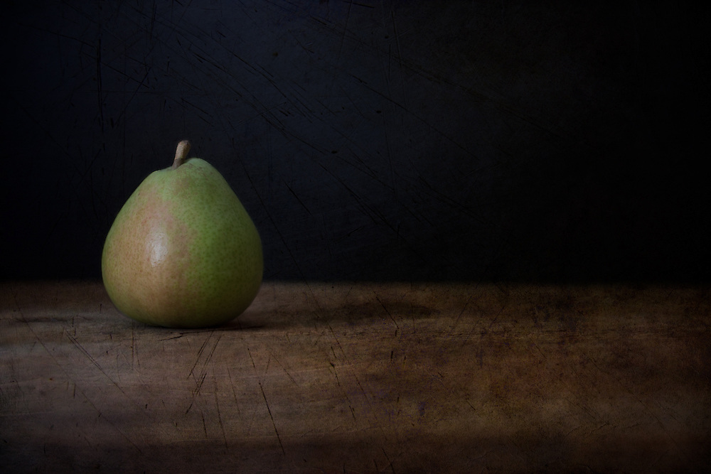 A rustic still life image of a Bartlett pear on an old rustic piece of wood and a dark background. Subtle green pear color with a hint of rose color. A long dark shadow adds just the right touch to balance the image. Rustic yet simplistic and a lovely addition to any kitchen or dining area. Photographed in my studio.
