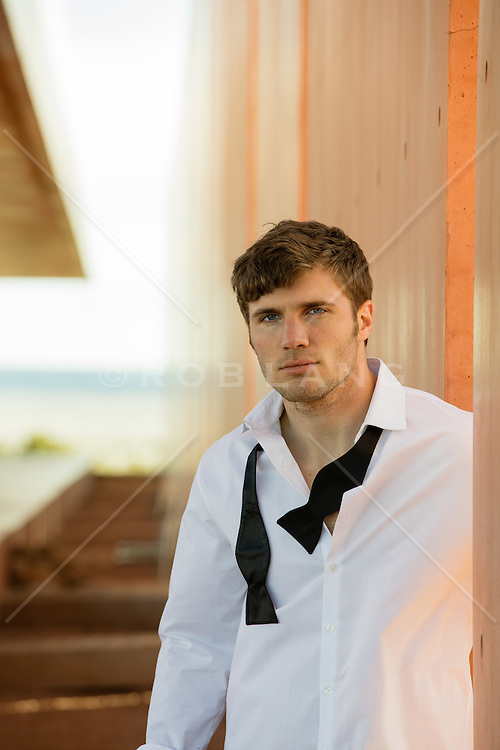 portrait of a handsome man in a tuxedo shirt and loose bowtie at a modern home