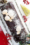 Traditional Buche de Noel with cinnamon meringue mushrooms on a white marble pastry board, sprinked with confectioners' sugar to evoke snow, and surrounded by symbols of the season - a Christmas tree candle, pine cones, a gift at lower right, red linen napkin, and holly berries.