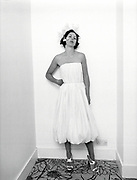 Isabella Blow wearing white dress leaning against wall with head tilted back.