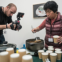 London, UK - 15 October 2014: a member of the press takes some shots at a woman serving soup made with vegetables from Fukushima, Japan at the Green Tea Gallery during the first day of Frieze Art Fair and Frieze Masters in Regent's Park.
