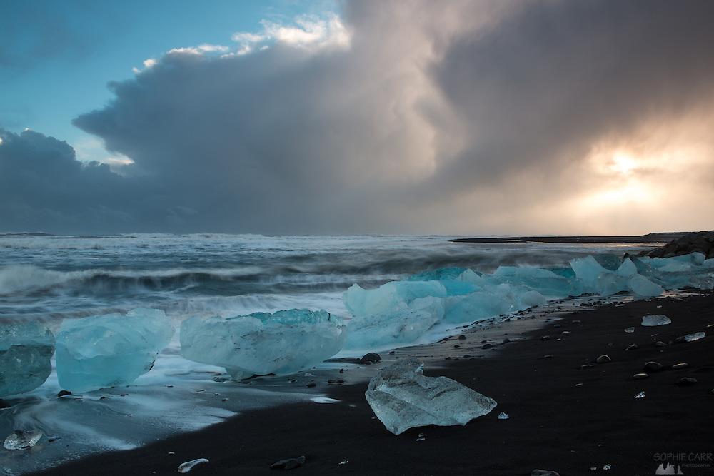 Waves crash over icebergs on Jökulsárlón Beach, leaving picturesque water trails