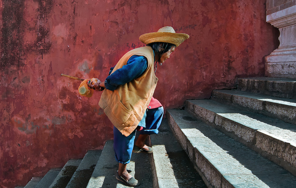 An old woman climbing the steps at the ancient city gate in Jianshui, Yunnan, China.