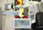© Licensed to London News Pictures. 08/10/2014. Richmond, UK. A model of Her Majesty the Queen at a workers desk.  The Mayor of London, Boris Johnson, and Zac Goldsmith MP tour 'The Poppy Factory' in Richmond, Surrey, today 9th October 2014.  Melanie Waters, the Chief Executive, briefed the Mayor and Zac Goldsmith on The Poppy Factory's 'Getting You Back to Work' initiative. To date, The Poppy Factory has supported nearly 500 wounded, injured or sick ex-service men and women back into the workplace through this new, nationwide initiative, through connections with commercial organisations like Transport for London. The goal is to help over 1,000 veterans by 2018. Employees at The Poppy Factory have made some 13 million poppies, 950,000 thousand remembrance crosses and 96,000 wreaths for The Royal British Legion Remembrance events in November. The Annual Field of Remembrance at Westminster Abbey is also planned and delivered by The Poppy Factory. Photo credit : Stephen Simpson/LNP