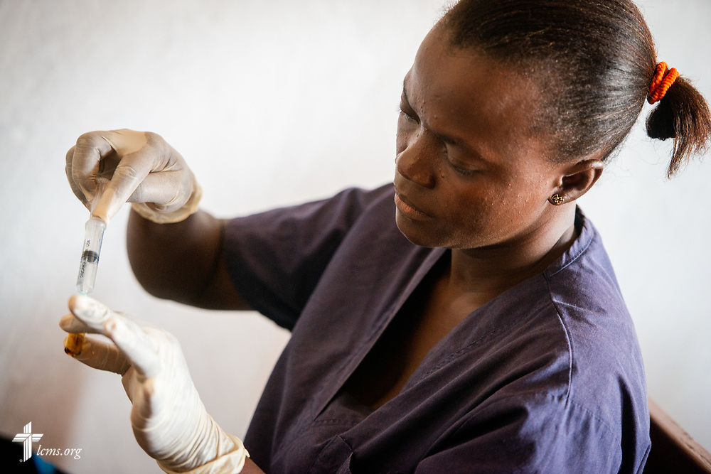 Rugiatu Kamande, a Sierra Leonean nurse with the team, prepares an injection for a patient on the fifth day of the LCMS Mercy Medical Team on Friday, May 11, 2018, in the Yardu village outside Koidu, Sierra Leone, West Africa. LCMS Communications/Erik M. Lunsford