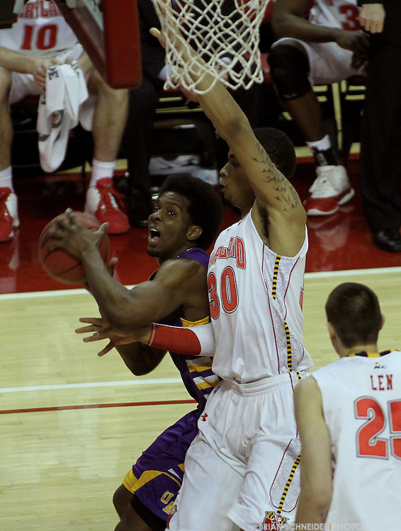 December 28, 2011; Baltimore, MD, USA; Albany Great Danes guard Gerardo Suero (20) attempts a layup against Maryland Terrapins forward Ashton Pankey (30) during the first half at the Comcast Center in College Park, MD. Brian Schneider-www.ebrianschneider.com