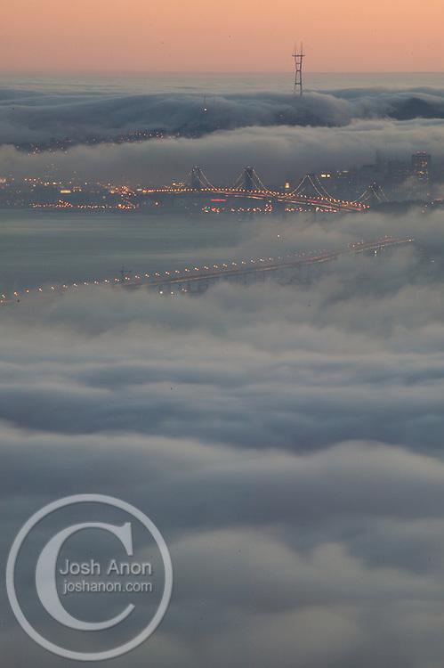 USA, Berkeley, California A fog bank seen from the Berkeley hills rolls into the San Francisco bay, covering the bay bridge. Credit as: © Josh Anon / Jaynes Gallery / DanitaDelimont.com