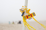 A mini kite rests on an umbrella stand on a foggy,windy day in Newport, oregon