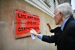 "© Licensed to London News Pictures. 07/10/2019. London, UK. Extinction Rebellion activists are seen spray painting at words ""LIFE NOT DEATH FOR MY GRANDCHILDREN"" on the wall of The Treasury in Westminster. Activists plan to converge on Westminster blockading roads in the area for at least two weeks calling on government departments to 'Tell the Truth' about what they are doing to tackle the Emergency. Photo credit: Ben Cawthra/LNP"