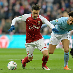 Mesut Ozil of Arsenal holds off Leroy Sane of Manchester City