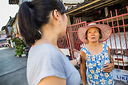 28 MARCH 2013 - BANGKOK, THAILAND:  Michelle Kao (left) talks Juan, a woman who lives in her neighborhood.    PHOTO BY JACK KURTZ