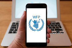 Using iPhone smartphone to display logo of WFP, World Food Programme