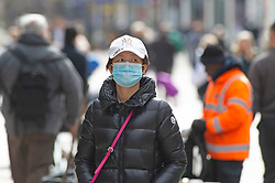 ©Licensed to London News Pictures 17/03/2020<br /> Bromley, UK. A lady wearing a protective face mask as she walks down Bromley high street. People out and about in Bromley High Street, Greater London after the Prime minister Boris Johnson asked people to avoid all non-essential travel because of the threat of Coronavirus. Photo credit: Grant Falvey/LNP
