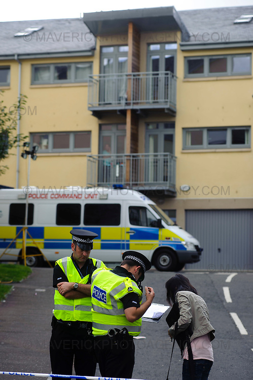 EDINBURGH, UK - 5th August 2010:  Police in Edinburgh are continuing the forensic examination of a flat on Edinburgh's Slateford Road after three children at the centre of a custody battle were discovered dead at the premises.  The grim discovery came after emergency services were called out to the house following reports of a gas explosion just before 3pm yesterday.  Pictured police take details from a local resident at the scene.  (Photograph: Callum Bennetts/MAVERICK)