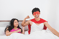 Portrait of excited man in superhero costume with woman on bed