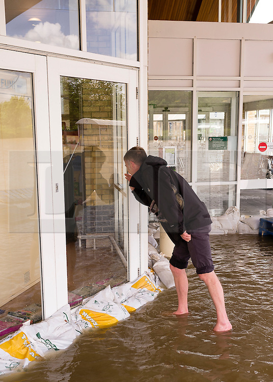 © Licensed to London News Pictures. 09/06/2012. London, UK. A man looks through the flooded enhance of a Morrisons Supermarket. The River Rheidol, swollen after two days heavy rain, and with a high tide forcing the waters back, bursts its banks and floods low-lying areas of shops and houses on the outskirts of Aberystwyth Wales UK. Photo credit : Keith Morris/LNP
