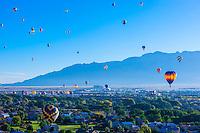 Hot air balloons flying (with the Sandia Mountains in background) at the Albuquerque International Balloon Fiesta, Albuquerque, New Mexico USA.