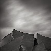 Monochrome photograph of the Walt Disney Concert Hall in Los Angeles, CA. A Long exposure captures the motion of clouds during a winter rain storm.