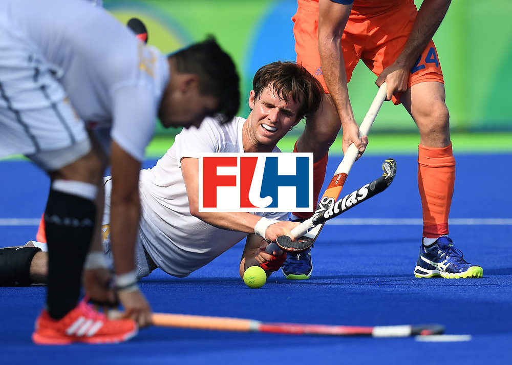 Canada's Adam Froese (C) pass the ball from the ground during the men's field hockey Netherlands vs Canada match of the Rio 2016 Olympics Games at the Olympic Hockey Centre in Rio de Janeiro on August, 9 2016. / AFP / MANAN VATSYAYANA        (Photo credit should read MANAN VATSYAYANA/AFP/Getty Images)