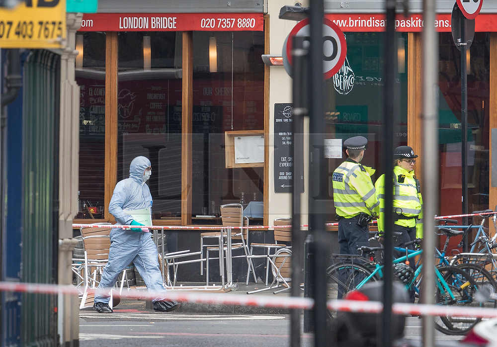© Licensed to London News Pictures. 05/06/2017. London, UK. A police forensic officer passes the Brindisa cafe in Borough Market as investigations continue following a terrorist attack on Saturday evening. Three men attacked members of the public  after a white van rammed pedestrians on London Bridge.   Ten people including the three suspected attackers were killed and 48 injured in the attack. Photo credit: Peter Macdiarmid/LNP