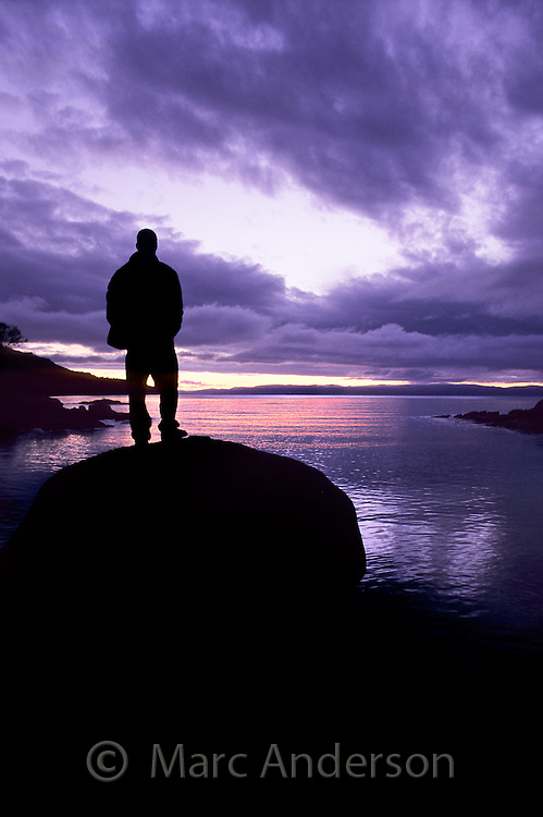 Man silhouetted against a sunset and looking out at a bay, Honeymoon Bay, Freycinet Peninsula, Tasmania.