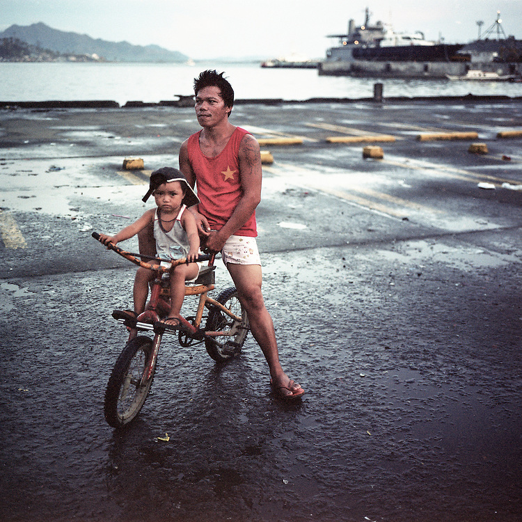 A boy and his father share a bicycle.<br /> <br /> Typhoon Haiyan, or locally known as Yolanda, the most powerful storm ever recorded, struck the southern part of Philippines on November 8, 2013 triggering flash floods and strong winds up to 200 miles/hr that caused a catastrophic damage to the region. Many towns and cities were devastated. Over 6000 people have been confirmed dead and thousands are still missing and displaced.