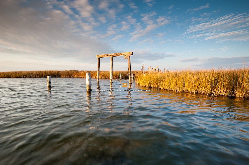 Sunset catches marsh grass and abandoned timber pilings in the sound at Pea Island National Wildlife Refuge.  At some point it would appear that a bridge carried traffic of some sort over the marsh waters to an unknown destination.