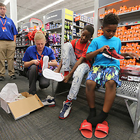 North Mississippi Boys & Girls Club members Javien Osborne, 12, center right, 12, and Jamere Smith, 9, get a little help trying on shows from Academy Sports clerk Crystal Noone as 30 members of the club received $100 girt cards as back to school gifts from the company.