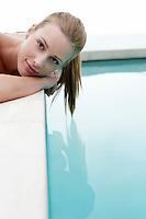 Women lying at edge of swimming pool portrait