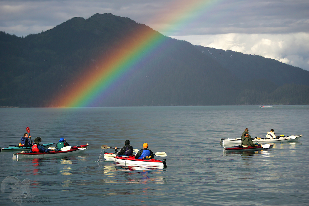 A group of kayakers stop to take pictures of a magnificent rainbow in Passage Canal in Prince William Sound near Whittier, Alaska