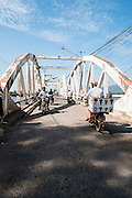 Motorcycles cross the Old Bridge over the Kampot river