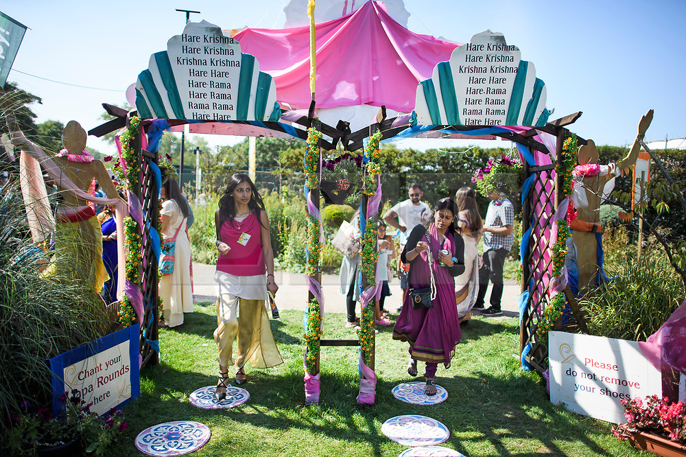 © Licensed to London News Pictures. 02/09/2018. Aldenham, UK. Followers of Hare Krishna branch of Hinduism pass through a floral archway as they queue to enter Bhaktivedanta Manor, Hare Krishna Temple in Aldenham, Hertfordshire during celebrations for the Janmashtami festival. Janmashtami is an annual Hindu festival that celebrates the birth of Krishna. Bhaktivedanta Manor, the venue fo the event, was donated to the Hare Krishna movement in February 1973 by former Beatle George Harrison. Photo credit: Ben Cawthra/LNP