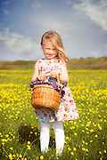 a 3 year old girl with a basket on a flower meadow