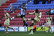 Sheyi Ojo of Wigan Athletic and Souleymane Bamba of Leeds United challenge for the ball. Skybet football league championship match , Wigan Athletic v Leeds Utd at the DW Stadium in Wigan, Lancs on Saturday 7th March 2014.<br /> pic by Chris Stading, Andrew Orchard sports photography.