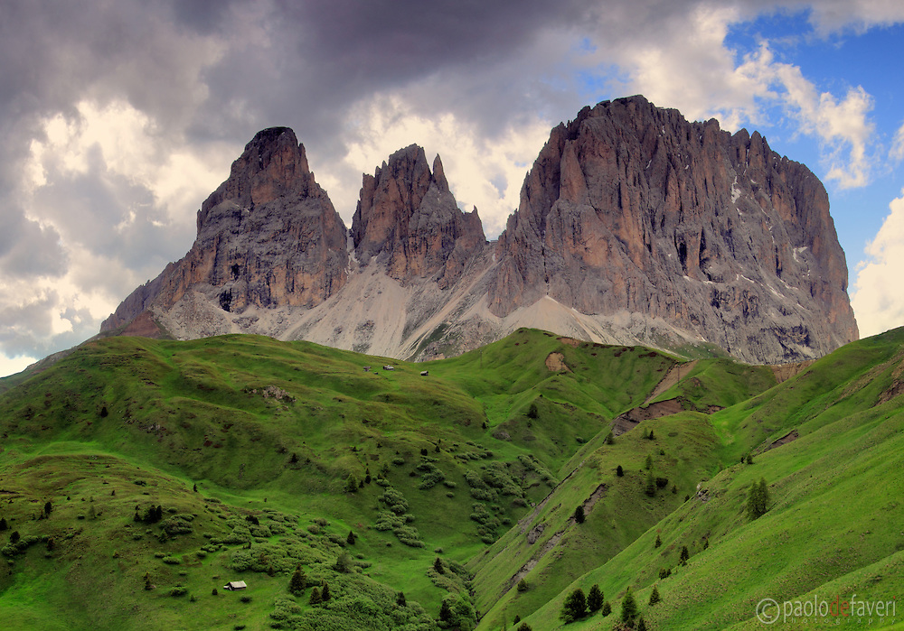 The amazing, jagged rocky peaks of the Dolomites known as Sasso Lungo and Sasso Piatto, emerging from the green prairies of Passo Sella, an high altitude pass in the province of Trento, Italy, linking Canazei to Selva di Val Gardena.