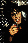 A drag queen, smiling drinking through a straw, 1999