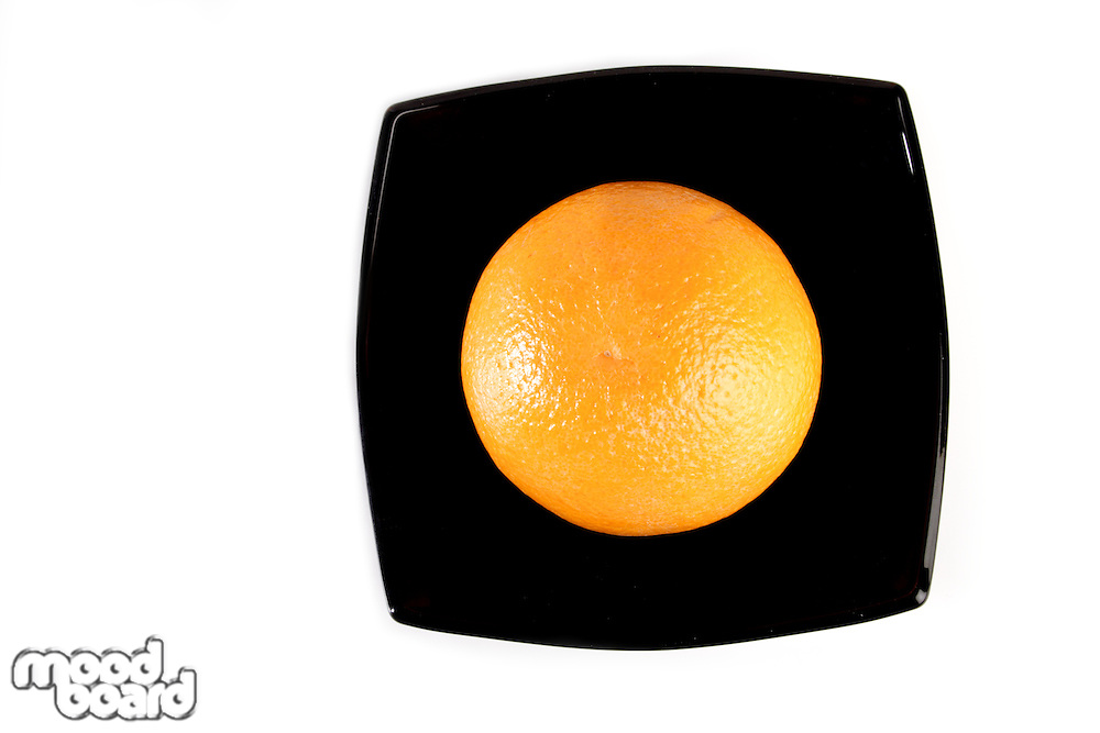 Orange in black bowl on white backgrond