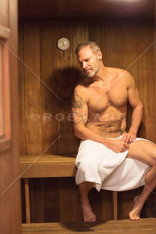 hot man sitting in a sauna