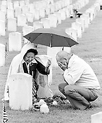 A Cherokee couple weep as they conduct a small private ceremony at the headstone of their fallen son, who died in Vietnam, at the National cemetery in Ft. Gibson, OK.