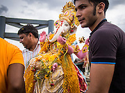 """15 SEPTEMBER 2013 - BANGKOK, THAILAND: Hindus in Bangkok carry statues of Ganesha to a waiting boat for the immersion on the last day of Ganesha Chaturthi celebrations at Shiva Temple in Bangkok. Ganesha Chaturthi is the Hindu festival celebrated on the day of the re-birth of Lord Ganesha, the son of Shiva and Parvati. The festival, also known as Ganeshotsav (""""Festival of Ganesha"""") is observed in the Hindu calendar month of Bhaadrapada. The festival lasts for 10 days, ending on Anant Chaturdashi. Ganesha is a widely worshipped Hindu deity and is revered by many Thai Buddhists. Ganesha is widely revered as the remover of obstacles, the patron of arts and sciences and the deva of intellect and wisdom. The last day of the festival is marked by the immersion of the deity, which symbolizes the cycle of creation and dissolution in nature.  In Bangkok, the deity (statue) was submerged in the Chao Phraya River.         PHOTO BY JACK KURTZ"""