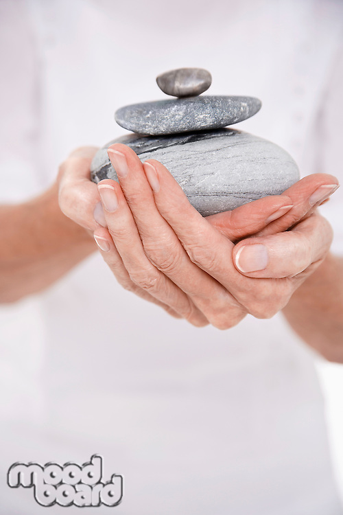 Woman Holding Pile of Stones mid section