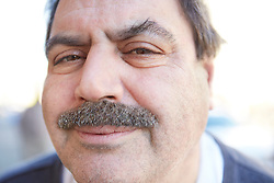 Portrait photograph of smiling middle age Italian guy with gray mustache